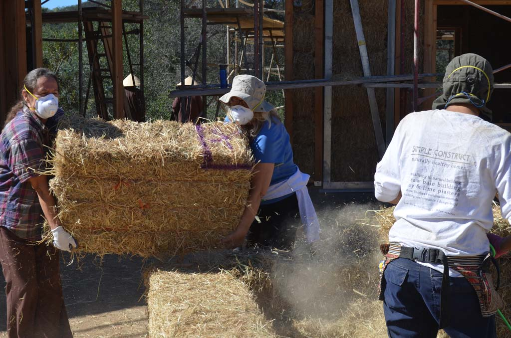 Volunteers helping to build the new straw bale structures at Deer Park Monastery bring a bale to be shaped to fit. Photo by Tony Cagala