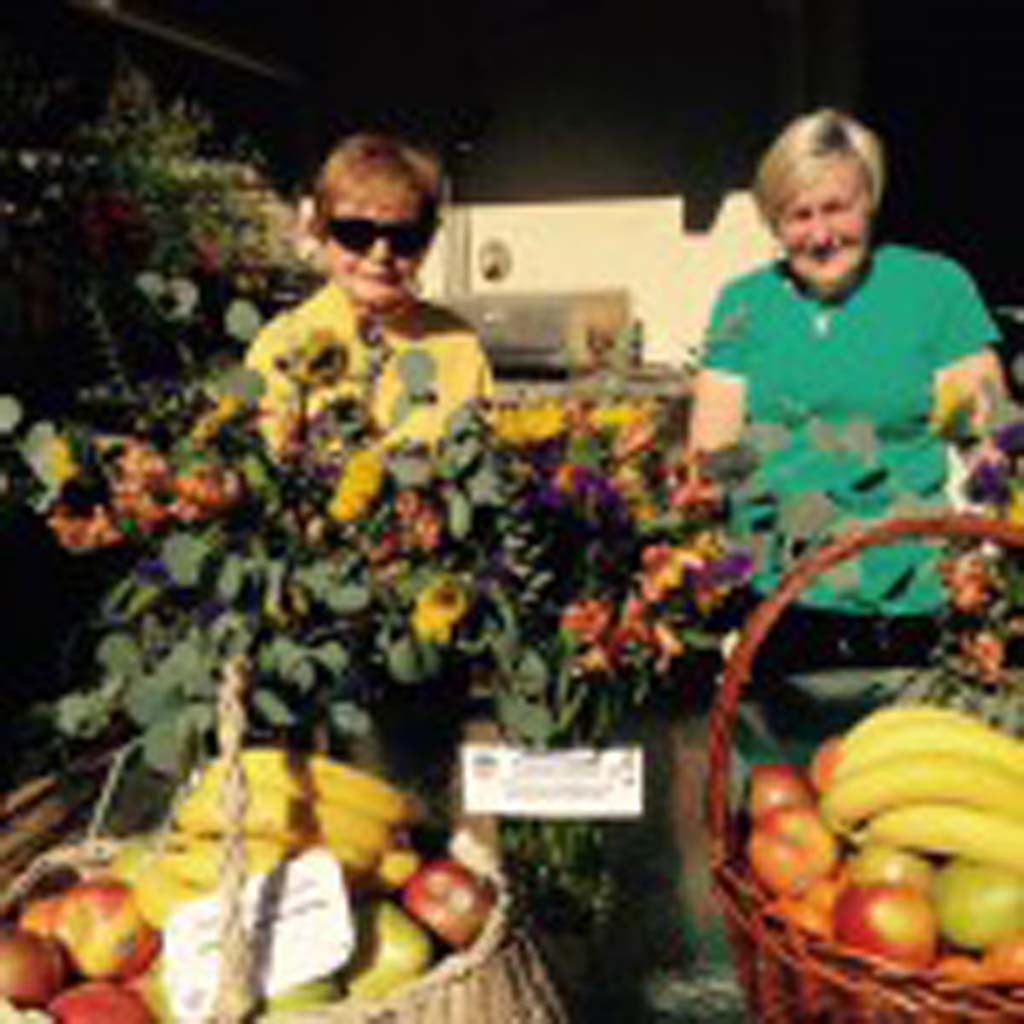Rancho Santa Fe Garden Club members LaVerne Scholosser and Shirley Corless prepare floral arrangements and fruit baskets. Courtesy photo