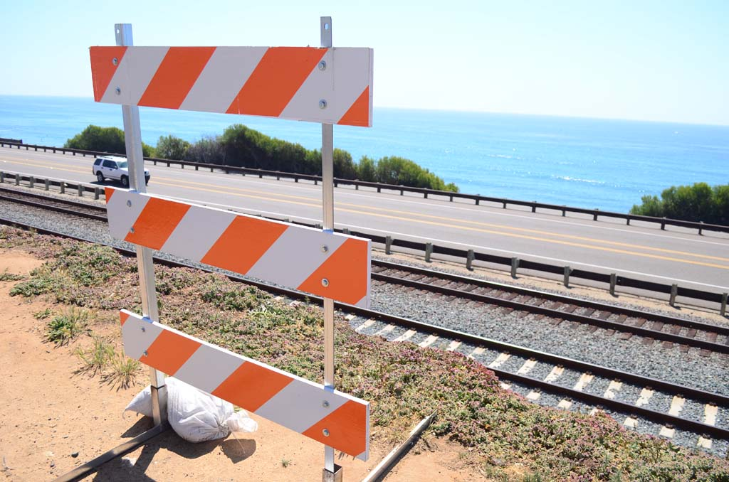 Barriers along San Elijo Avenue have some residents hoping they'll be taken down soon becuase of their unsightly appearance. The North County Transit District placed the barriers as a matter of public safety. Photo by Tony Cagala