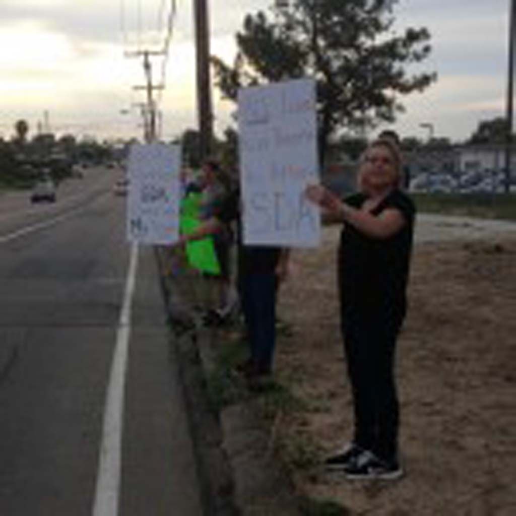 Nearly 40 parents and students rally outside of San Dieguito High School Academy this week to insist the district revise its enrollment policy. Photo by Aaron Burgin