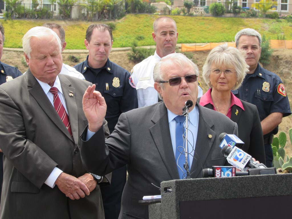 Carlsbad Mayor Matt Hall, at podium, talks about the importance of communication during the fires that broke out a year ago at a press conference with other county and emergency officials on Wednesday. Photo by Ellen Wright