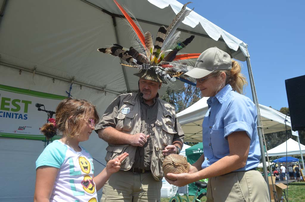 Bella Peirsol, 8, left, gets a chance to touch a three-banded armadillo with Dr. Zoolittle, center, and Rebecca Willetts, from the San Diego Zoo, during Encinitas' EcoFest. Photo by Tony Cagala