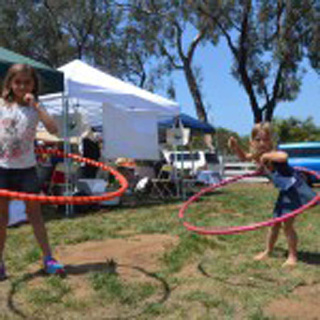 Peyton Gaspar, left, and Addison Gaspar, daughters of Encinitas Mayor Kristin Gaspar do some hula-hooping at the EcoFest. Photo by Tony Cagala