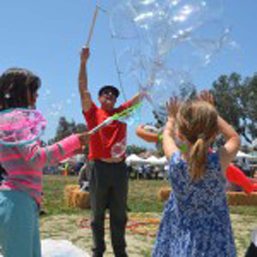 Steve Allen sends large bubbles into the sky for youngsters to try and catch. Photo by Tony Cagala
