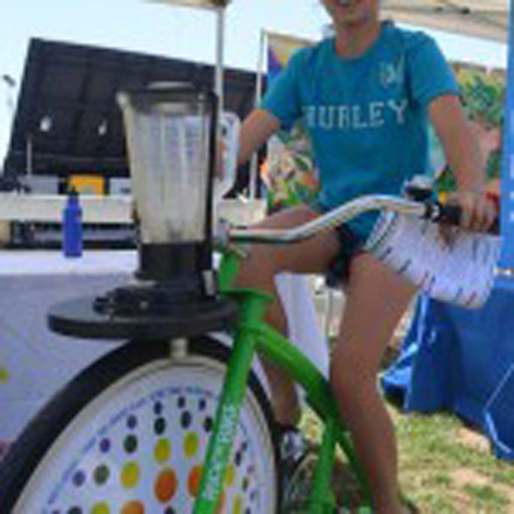 Alex Polito rides a bike attached to a blender mixing smoothies. Photo by Tony Cagala
