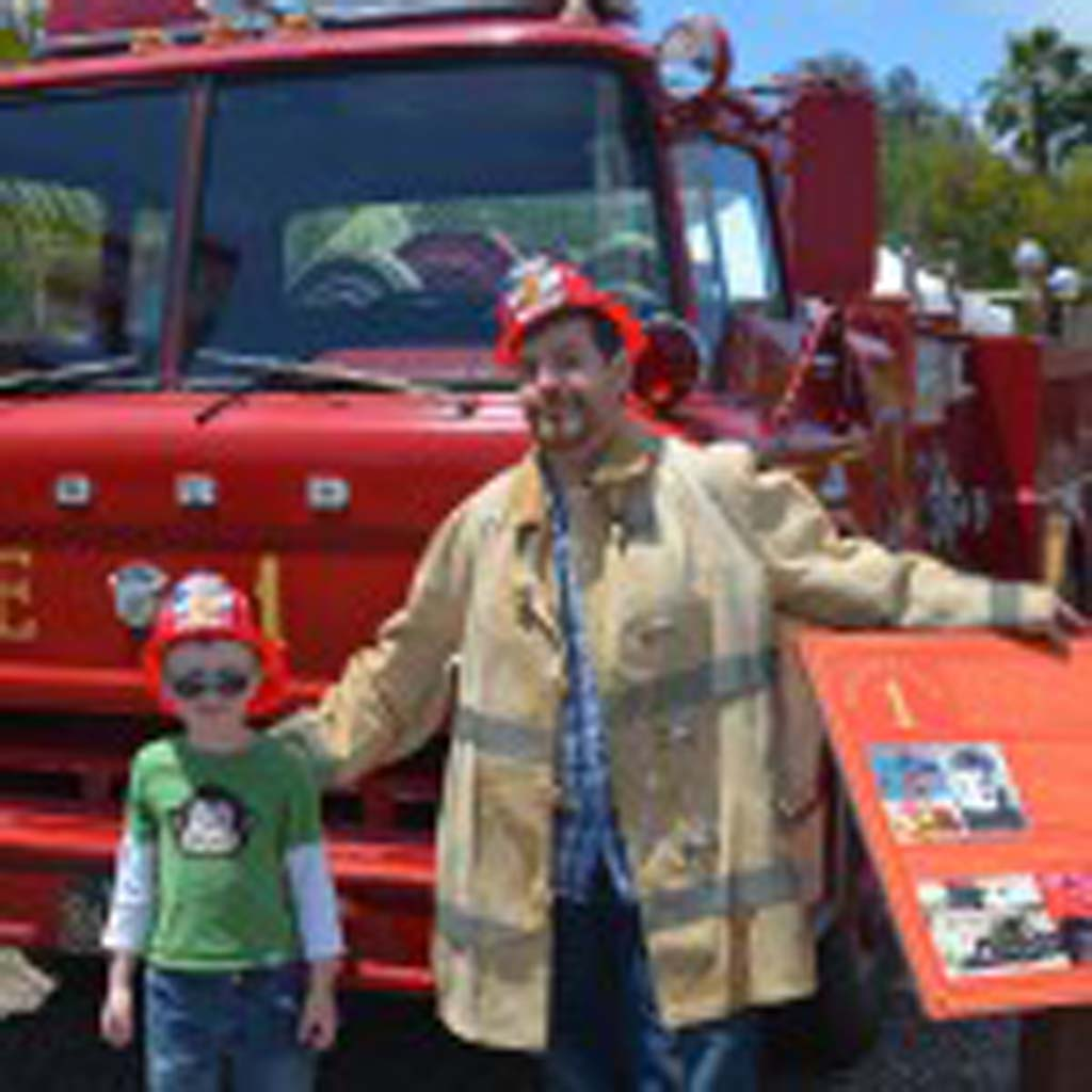 Mark Sinott, left, with his dad, Chris Sinnott dress up as firemen and pose next to a 1957 Del Mar Fire Department fire engine. Photo by Tony Cagala