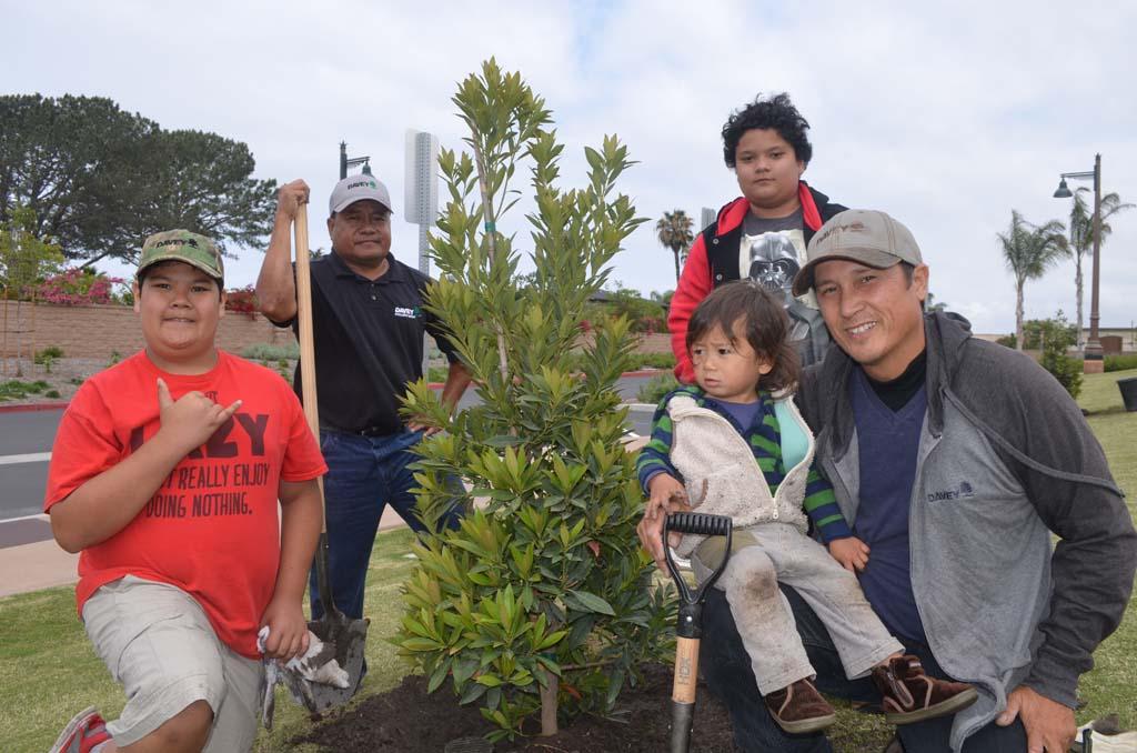 From left: Junior Felise, Nila Felise, Charlie Felise, Amon Greene and Tony Greene plant a tree during the Arbor Day celebration. Photo by Tony Cagala