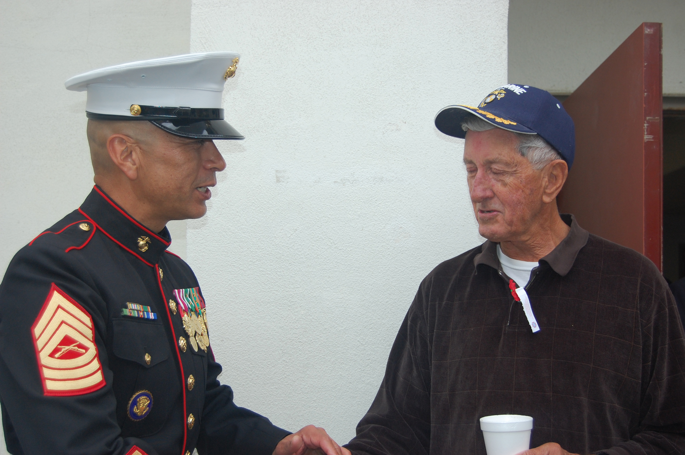 Guest speaker Master Sgt. Julian Gonzales chats with fellow Marine and Lake San Marcos resident Terry Thielen after the ceremony. Photo by Bianca Kaplanek