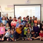 """John McCaw, holding a recently discovered John Lennon guitar, brought the instrument to Paula Intravaia's fourth-grade class at Carmel Del Mar Elementary School. Her husband, Marc Intravaia, far right, accompanied by TJ Klay, left, on harmonica, played """"Imagine"""" while the students sang along. Also pictured is McCaw's wife, Cathy. Courtesy photo"""