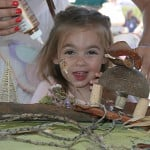 Quinlan Blackburn, 3, of La Jolla, gets a hand finishing her fairy house. There were close to a dozen craft stations at the festival. Photo by Promise Yee