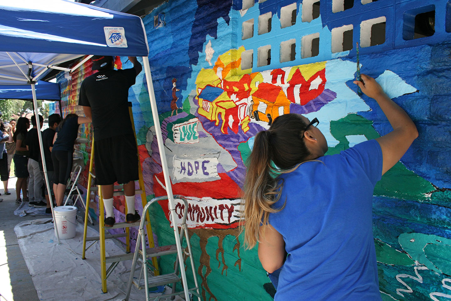 Teens from Project REACH pitch in to paint. The mural is part of a neighborhood beautification project. Photo by Promise Yee