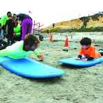 Logan Lowery, 6, of Encinitas, on right, practices before going out. Youth with multiple sclerosis, autism and other challenges spend a morning surfing. Photo by Promise Yee