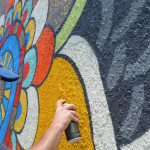 North County artist Skye Walker adds some color to his newest mural on the south facing wall of Royal Liquor in Leucadia. Walker did a mural on the north side of the building last year. Photo by Tony Cagala
