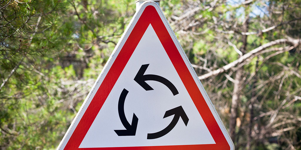 Roundabout triangle traffic sign on nature background. Stock photo