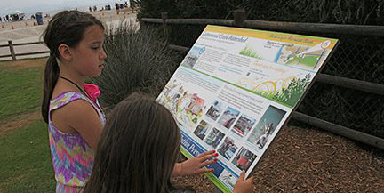Taylor Cullen, 5, of San Diego, and Makayla Charles, 9, of Fioria, Ariz., look at a city sign about the local watershed. A series of interpretive signs are posted along Cotton Creek. Photo by Promise Yee