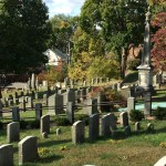 """Just a few of the hundreds of graves at the 90-acre Sleepy Hollow Cemetery stand in the autumn sunshine. Some of its well known residents include Andrew Carnegie (1835-1919); Walter Chrysler (1875-1940); Samuel Gompers (1850-1924); Leona Helmsley (1920-2007); and Washington Irving (1783-1859), whose short story, """"Legend of Sleepy Hollow, put the village on the map."""