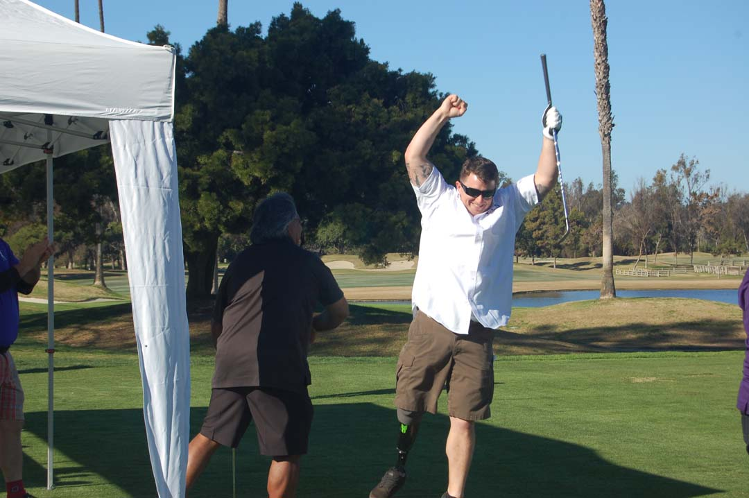 Marine veteran Dan Stoner jumps for joy after sinking a hole-in-one. Photo by Bianca Kaplanek