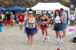 Amanda Brandlin from Dancing with Disaster throws while Brittany Gwin and Michelle Trembly, making up team On the Bottle, look on.