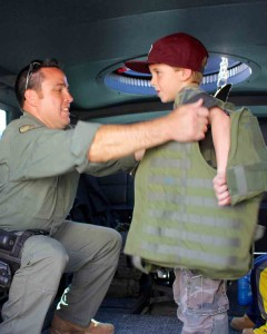 SWAT Officer Corey Kaldenbach helps Ayden Sellers, 6, of Oceanside, try on a police vest. Ayden wants to be a police officer.