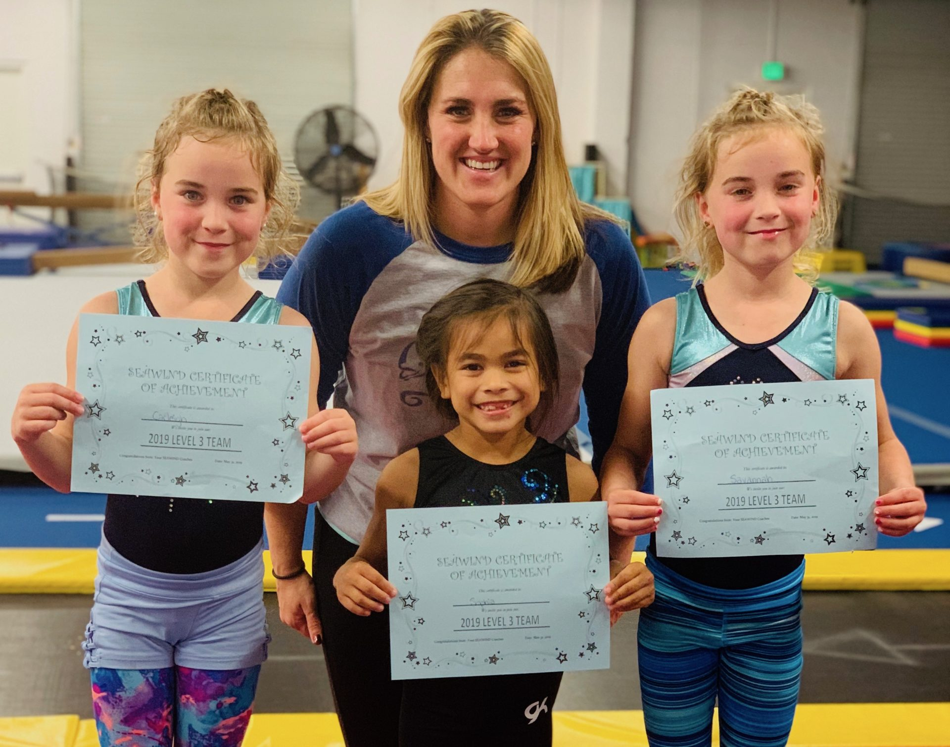 Lydia Jo Budny stands behind gymnastic students holding up awards