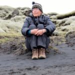 Janell Cannon sits in a lava field in Iceland