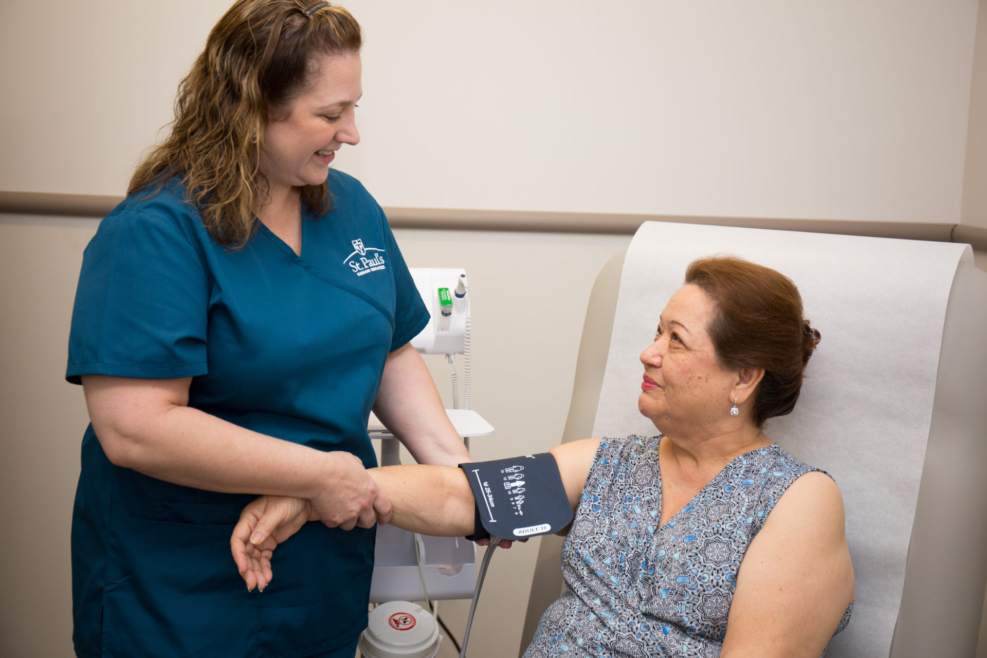 A nurse checks a patients blood pressure in hospital bed