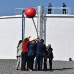 Group of people lift a red google maps location pin in front of a water plant