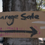A hand made cardboard sign for a garage sale that is taped to a tree