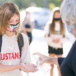 A young student wearing a mask gets hand sanitizer before entering school