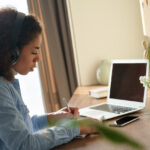 Focused african female student wears headphones elearning studying alone at home office desk. Millennial mixed race teen girl listening audio podcast e learning english language concept making notes.