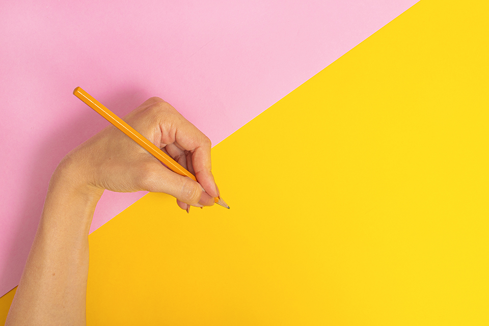 The left hand is holding a pencil and is about to write something on a bright pink-yellow background. International Left-handers Day on August 13