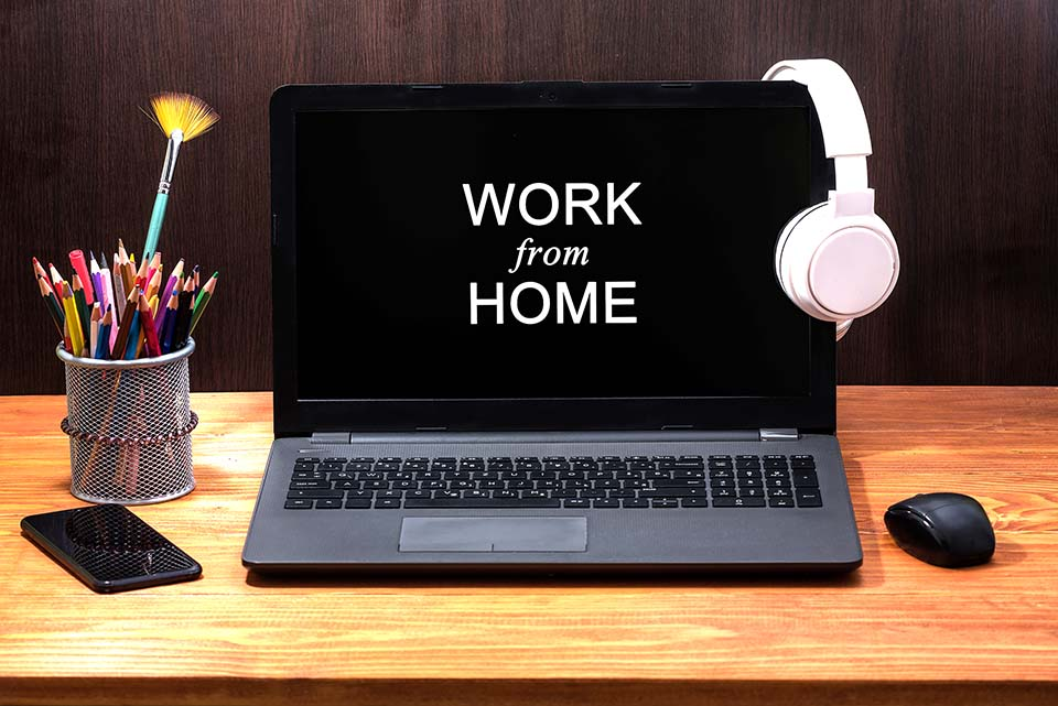 Work from home during Coronavirus pandemic quarantine isolation. Working remotely home concept. Comfortable working place in home office with laptop on the table with Headphones