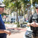 a member of Carlsbad Police Department's Homeless Outreach Team (HOT) speaks with a homeless resident in 2018. Staff photo