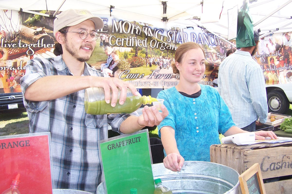 Young farmers, Sierra and Jacob from Morning Star Ranch, offer samples of their green juices at Leucadia Farmers' Market. Photo by Jano Nihgtingale