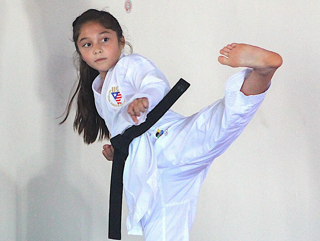 Carlsbad resident Lily Rashidi, 9, leads her karate class with warmup kicks on Sept. 15 at the Japan Karate-Do Organization building in Carlsbad. Photo by Steve Puterski