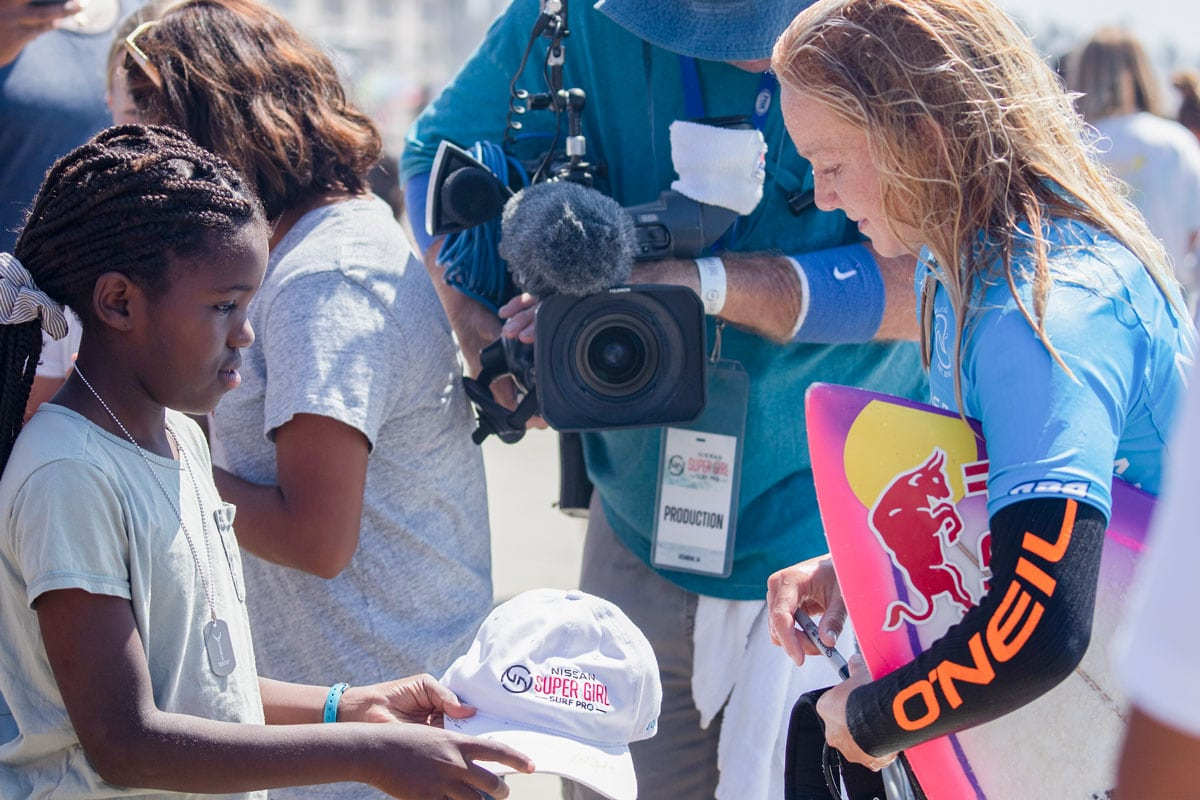 Oceanside's hometown hero Caitlin Simmers, 15, signs an autograph for a fan at the 14th annual Nissan Supergirl Surf Pro on Sunday in Oceanside. Photo by Kurt Steinmetz