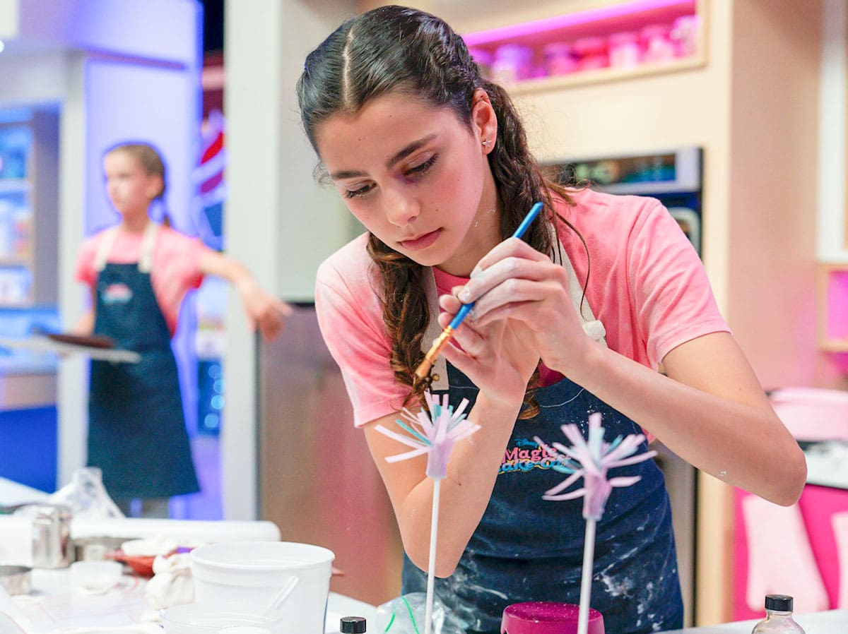 """Carlsbad's Ella Traverso works on a cake during the filming of an episode of """"Disney's Magic Bake-Off,"""" which aired on Aug. 20. Teammate Ellie Joyce works in the background. Courtesy Aaron Epstein/Disney"""