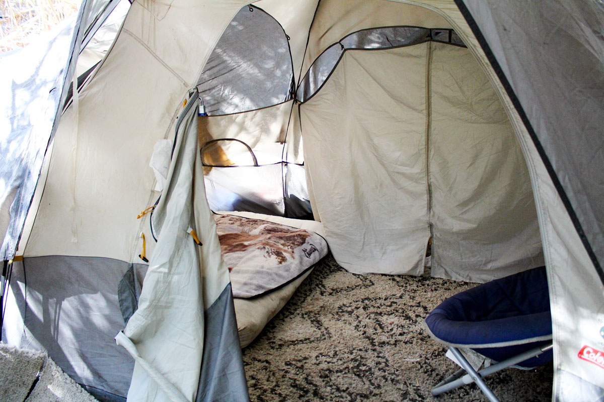 A tent equipped with a bed , chair and a makeshift carpet-sample walkway in a homeless camp near the I-5 north offramp in Encinitas. Photo by Jordan P. Ingram