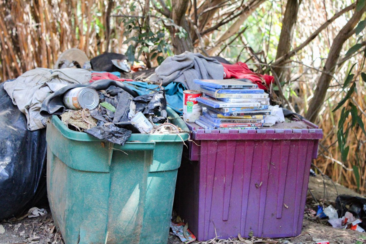 DVDs and clothes sit atop bins in a wooded area adjacent to Encinitas Boulevard. Photo by Jordan P. Ingram