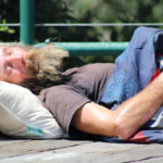 A homeless man sleeps on the overpass near Cottonwood Creek Park in the middle of the day on Aug. 9 in Encinitas. Photo by Jordan P. Ingram