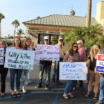 A group of residents hold signs outside of Encinitas City Hall on Wednesday night in opposition to the city's proposed relocation of the Safe Parking Lot to the Encinitas Community and Senior Center. The council approved the relocation site. Photo by Bill Slane