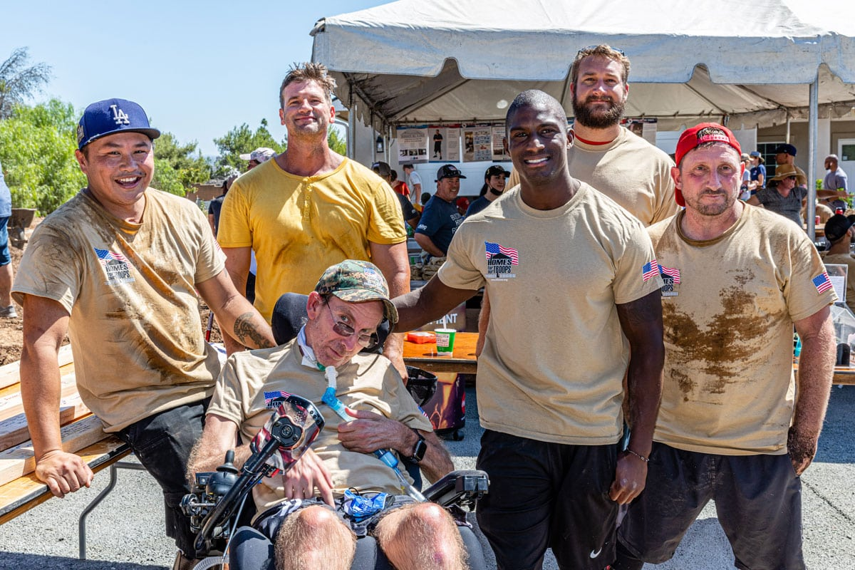 Marine 1st Sgt. Ben Holmes (far right) and Marine Cpl. Kionte Storey (second from right) at the volunteer day for Homes for Our Troops. Photo via Homes for Our Troops