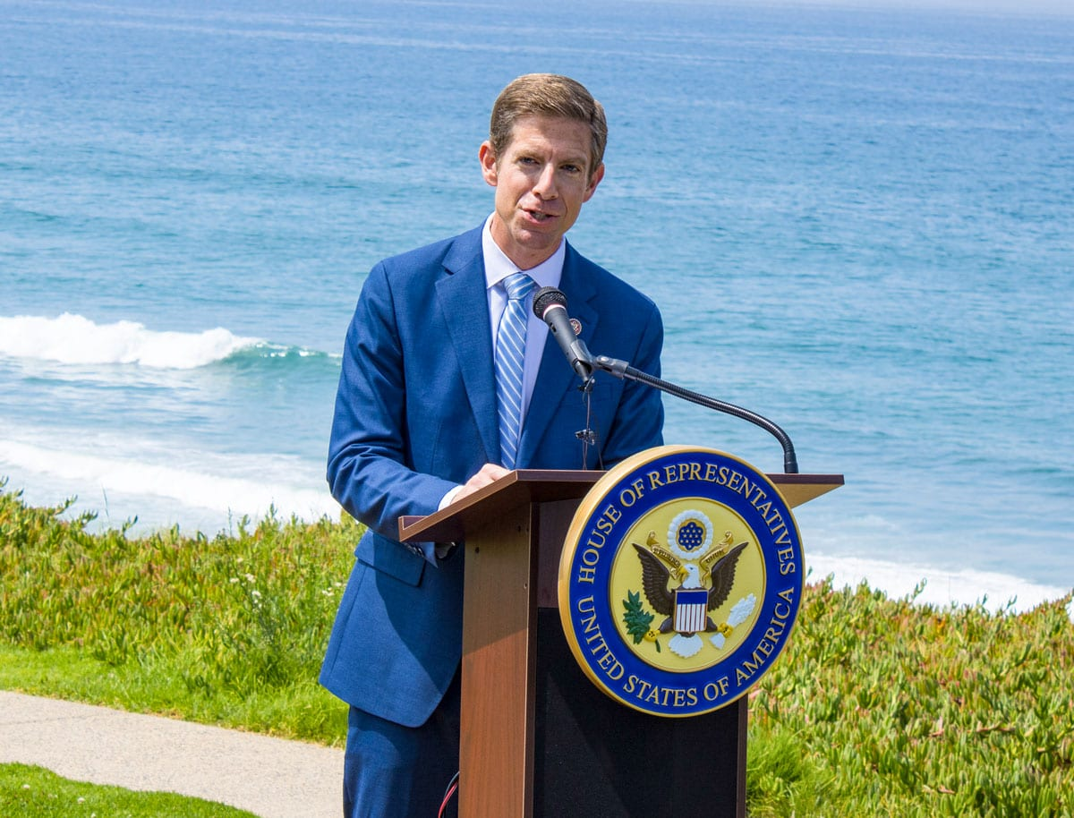 Rep. Mike Levin speaks Tuesday at Seagrove Park in Del Mar to focus on climate change policy and funding for projects related to moving the region's rail line away from the Del Mar bluffs. Photo by Bill Slane