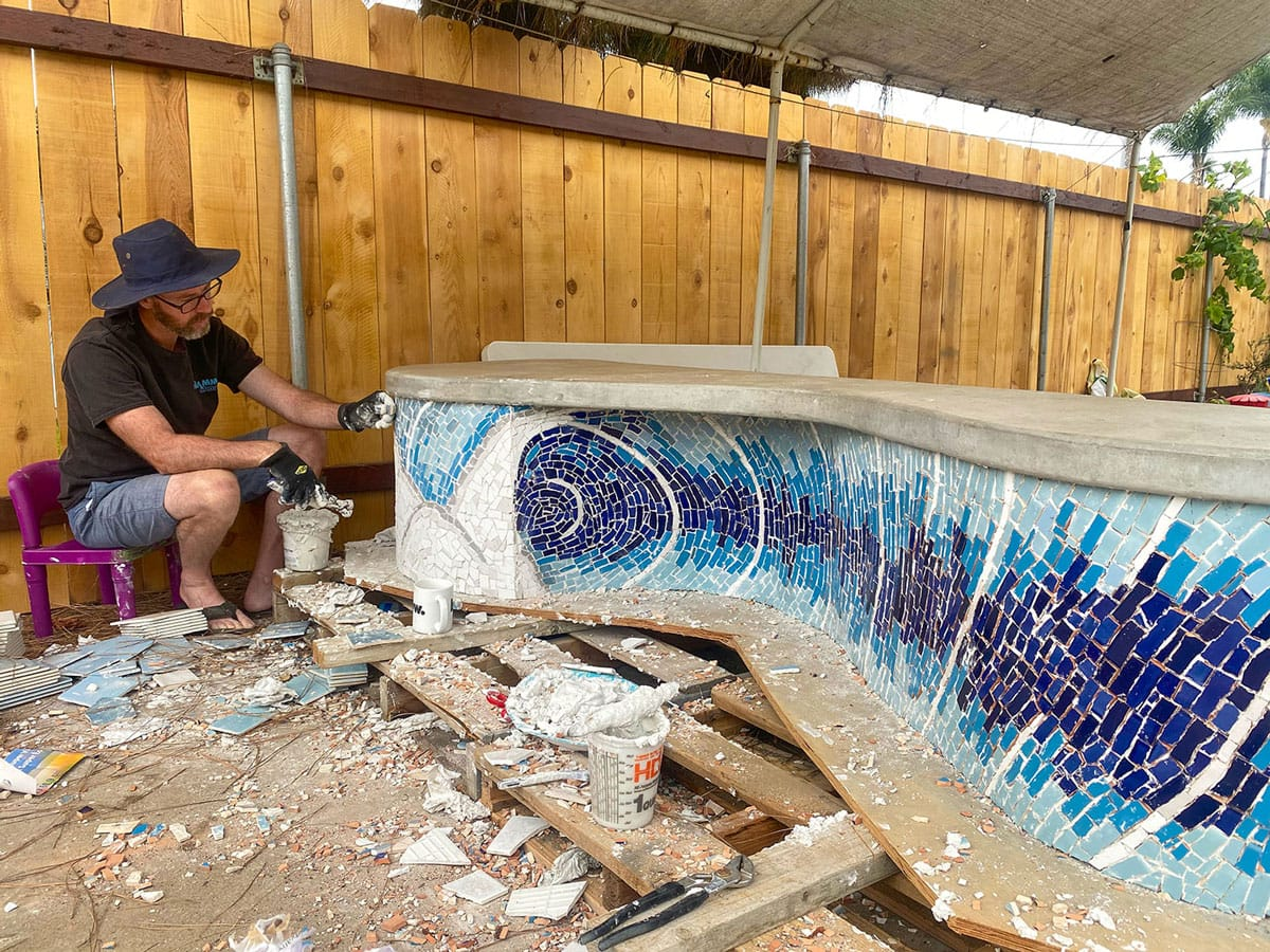 Carlsbad artist Bryan Snyder works on a mosaic for the Jack Munday Memorial Bench. Local mason Jeff Vaughn contributed masonry work for the project. Photo courtesy of Bryan Snyder