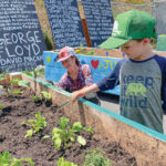 Local volunteers Lisa Elliot and her son Arthur finish painting one of several community garden beds at the Encinitas 4 Equality Multicultural Collective and Community Center along Coast Highway 101 in Encinitas